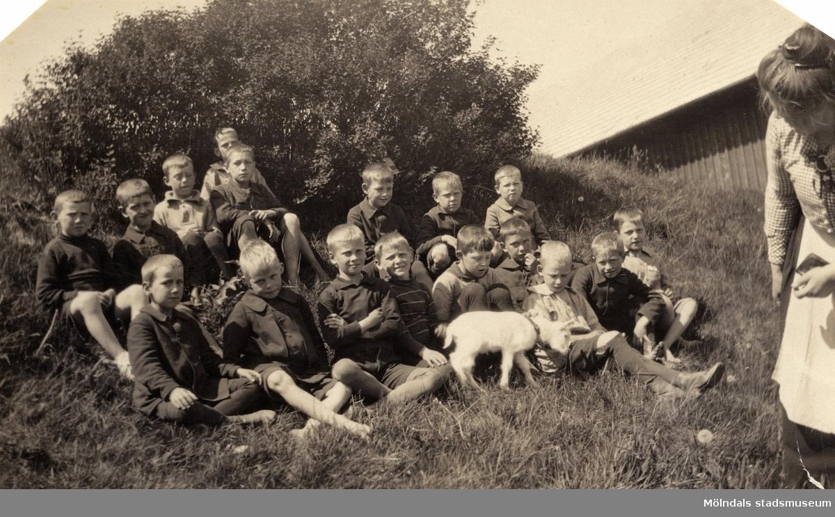 """Gruppfoto av skolklass. Pojkarna i klassen och en get. Fröken Klara Arvidsson. Övre raden, tredje fr.h.: Karl-Erik Marmgren. Direktören Martin Holterman i Ostindiska kompaniet ägde Åby gård. 1782 skänkte han 3000 daler silvermynt till Fässbergs församling + ett nybyggt skolhus och trädgård på gårdens ägor vid Åby by. I skolan skulle 10 fattiga barn undervisas i """"kristendom, skrivande och något räknande. Holtermans skola fanns kvar till 1875. Då hade donationens ändamål ändrats, och man byggde i stället ett barnhem kombinerat med småskola. 1914 brann barnhemmet och 1915 byggdes ett nytt barnhem på samma tomt. 1929 överlämnades barnhemmet till Mölndals stad."""