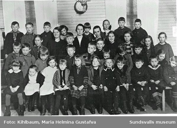 Söndagsskoleklass I Mellberg, Ljustorp. Textlappar med namn på barnen (stämmer inte helt) finns till fotografiet. Ester Näslund (söndagsskolelärarinna) ståeende längst upp under klockan. Valter Sundell (längst upp, 3:a fr v) Valfrid Sundell (längst upp, 2:a fr h) Irene Sundell (övre 2:a raden, 3:a fr h).
