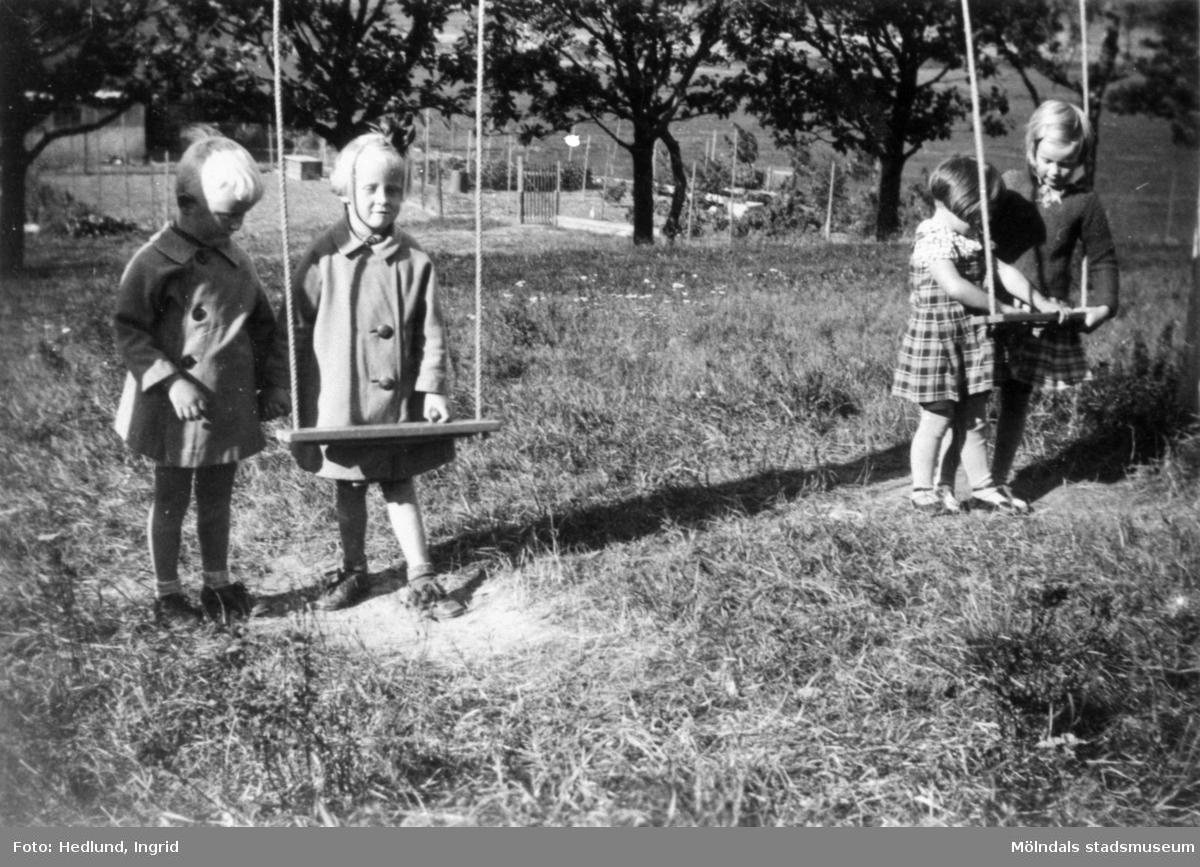 Bosgårdens barnträdgård 1938. Fyra barn som står parvis vid var sin gunga.