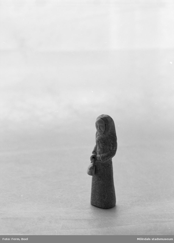 En kvinnofigur med dok och handväska. Inlämnat förslag till en tävling 1992 om souvenir för Mölndal.