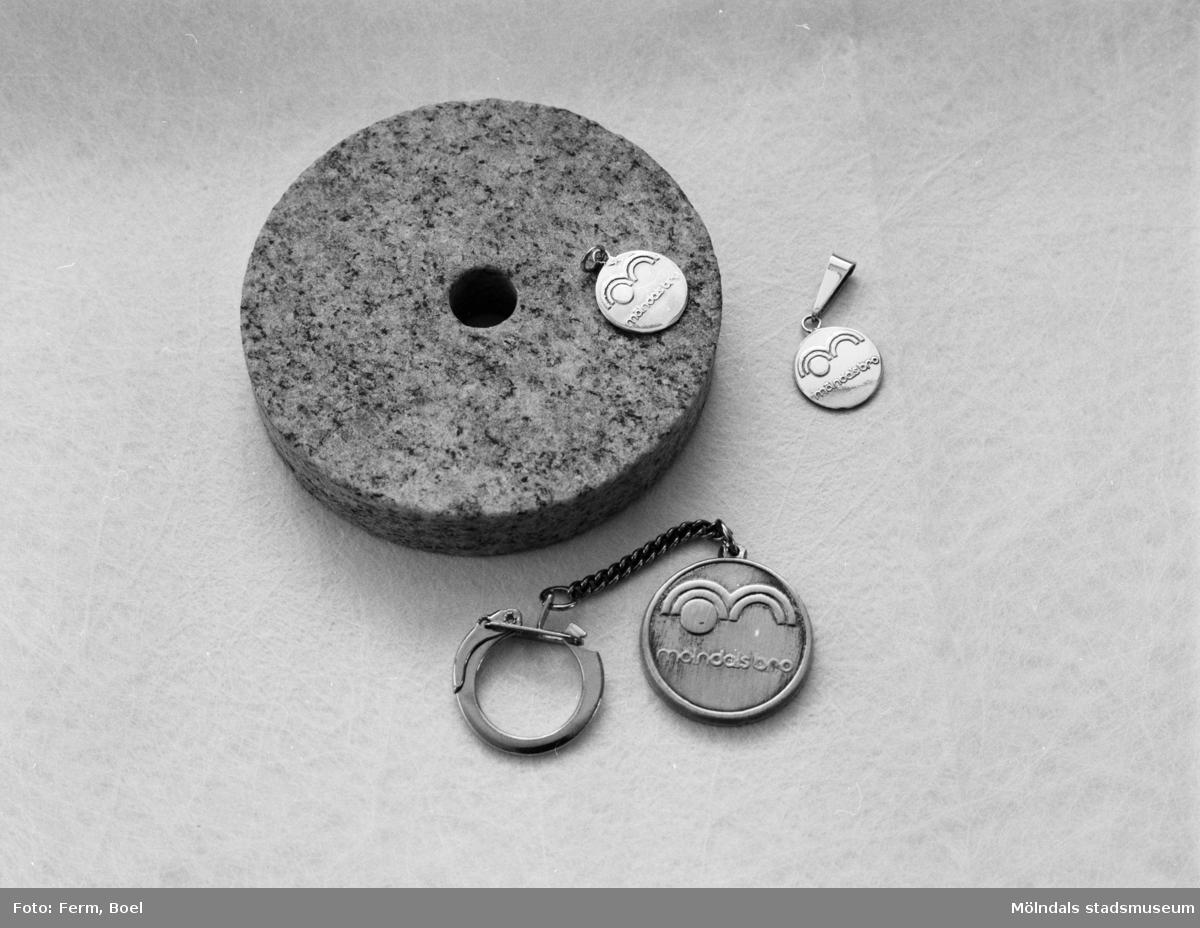 """En ca 10 cm rundsvarvad stenplatta med hål i. En nyckelring samt två hängsmycken med inskriptionen """"mölndalsbro"""". Inlämnat förslag till en tävling 1992 om souvenir för Mölndal."""