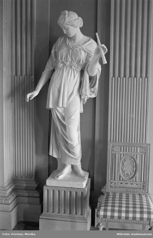Dokumentationsfoto från Gunnebo slott våren 1992. Inredningsmiljö, konstföremål och möbler av varierande slag. Här ses en kvinnlig skulptur med en flöjt i ena handen, ståendes vid en vägg.