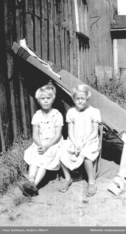 Två flickor (Ulla Vesterberg och Birgit Karlsson) tältar med en filt som är fastspikad i väggen. De sitter på bakgården till Kvarnfallet 31, 1930-tal. Bostadshuset tillhörde Carlsfors fabriker.