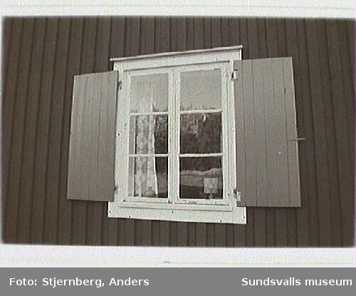 Fd sågställar bostad, nu sommarstuga. Fönster på norra gaveln. En helbåge med handblåst glas.