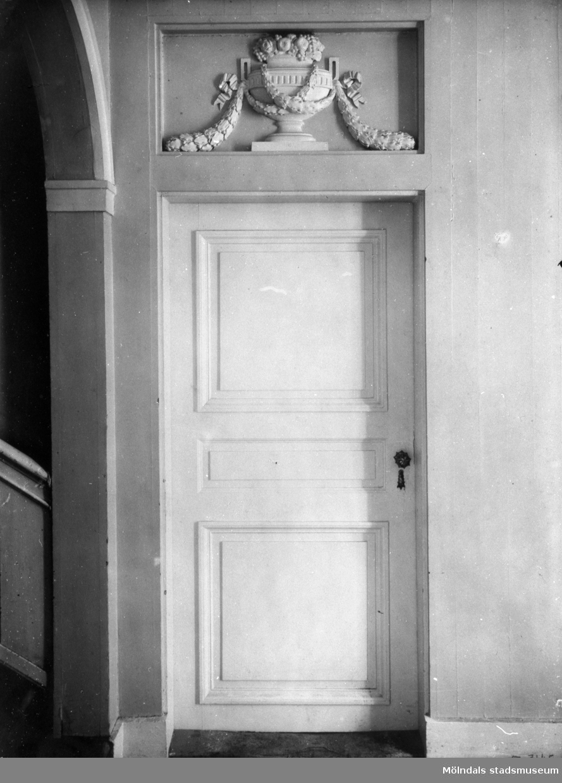 Enkeldörr med relief ovan som är en fruktskål av trä. Dörren går mellan Dégagementet och Östra förstugan i huvudvåningen på Gunnebo slott.