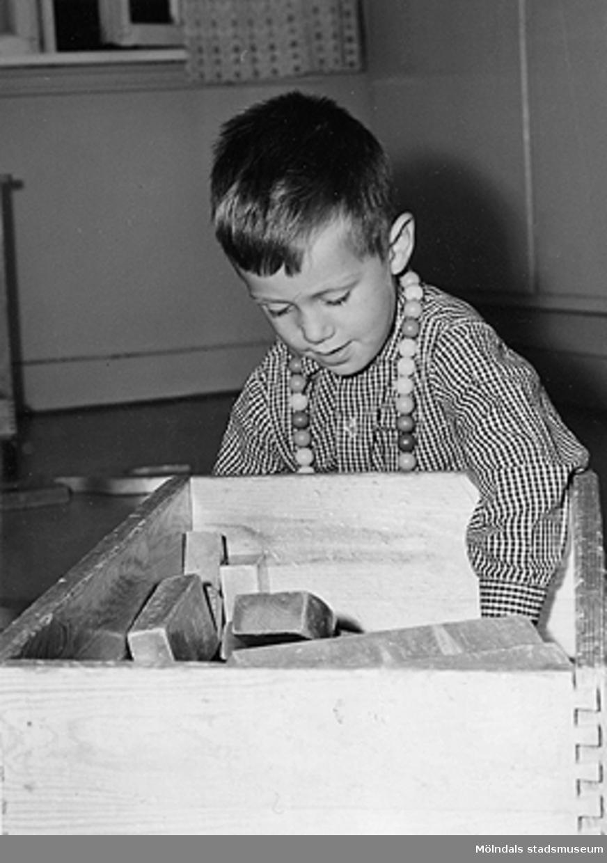En pojke som leker med träklossar vid Holtermanska daghemmet 1953.