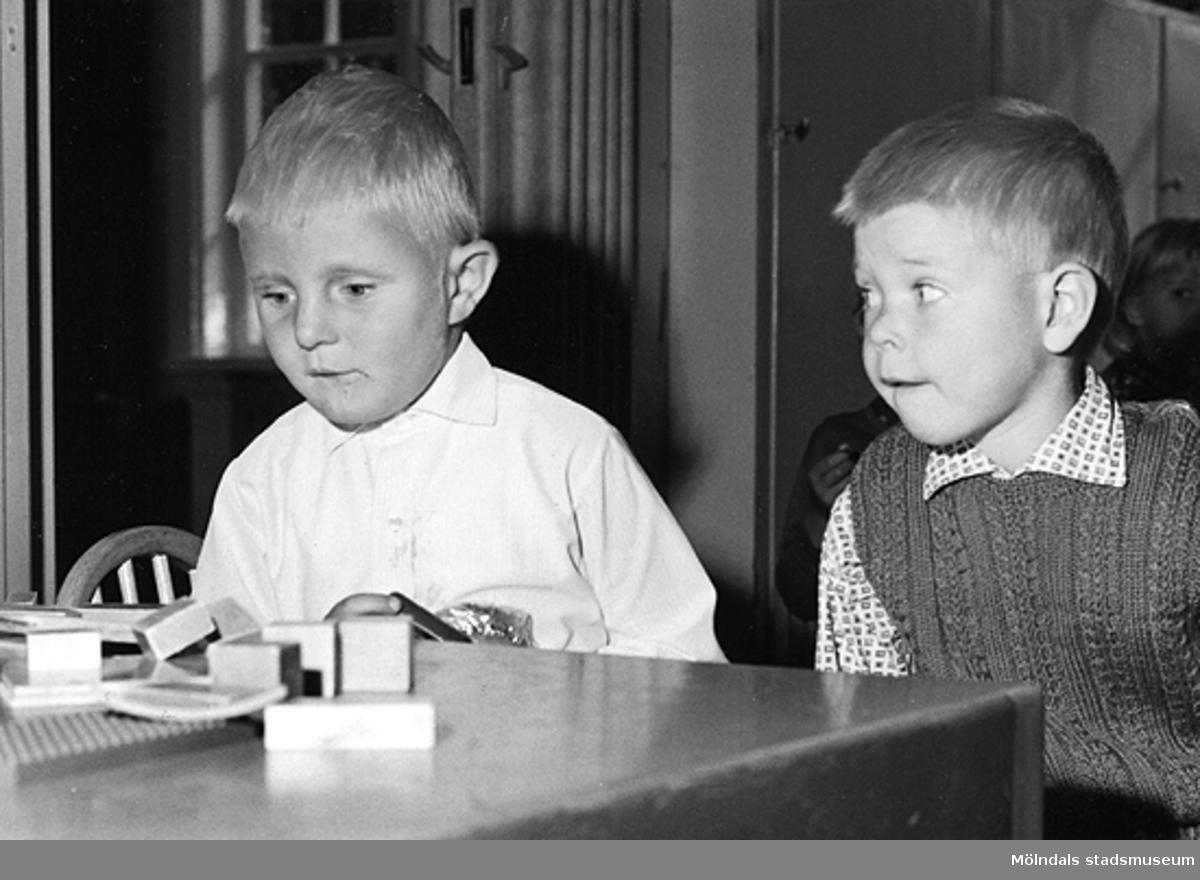 Två pojkar som leker vid ett bord. Holtermanska daghemmet 1953.