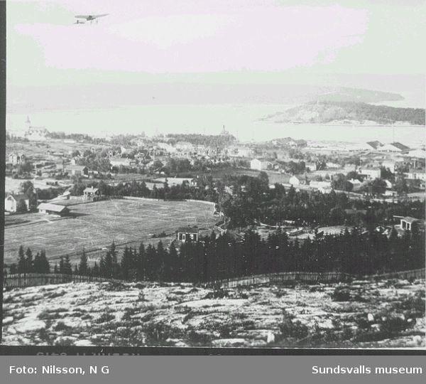 Vy från Södra berget. Skönsmons kyrka, Kubikenborgs sågverk, herrgård mm samt  Tjuvholmen. Baron Carl Cederströms uppvisningsflygning i Sundsvall.