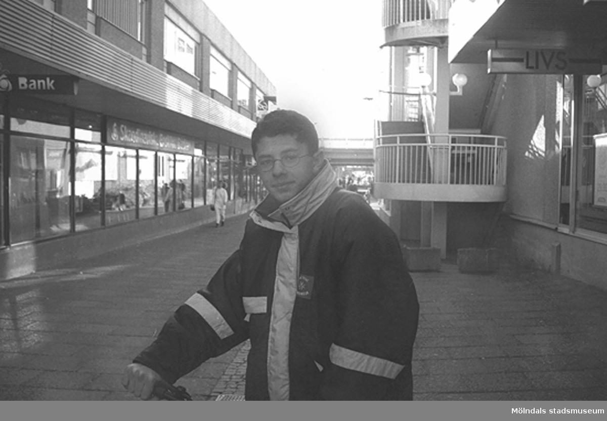En kille som står på Nygatan. Mölndalsbro i dag - ett skolpedagogiskt dokumentationsprojekt på Mölndals museum under oktober 1996. 1996_1079-1097 är gjorda av högstadieelever från Kvarnbyskolan 9C, grupp 4. Se även 1996_0913-0940, gruppbilder på klasserna 1996_1382-1405 samt bilder från den färdiga utställningen 1996_1358-1381.