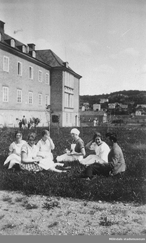 Bilden är tagen på södra sidan av Mölndals lasaretts gamla byggnad. I  bakgrunden ses stadsdelen Trädgården. Damerna på bilden är okända.