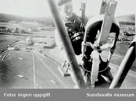 Reparatör Lennart Gustafsson vid arbete på den provisoriska fackverksmasten, 1948. Nedan i bakgrunden ses rundradiostationen i Ljustadalen.