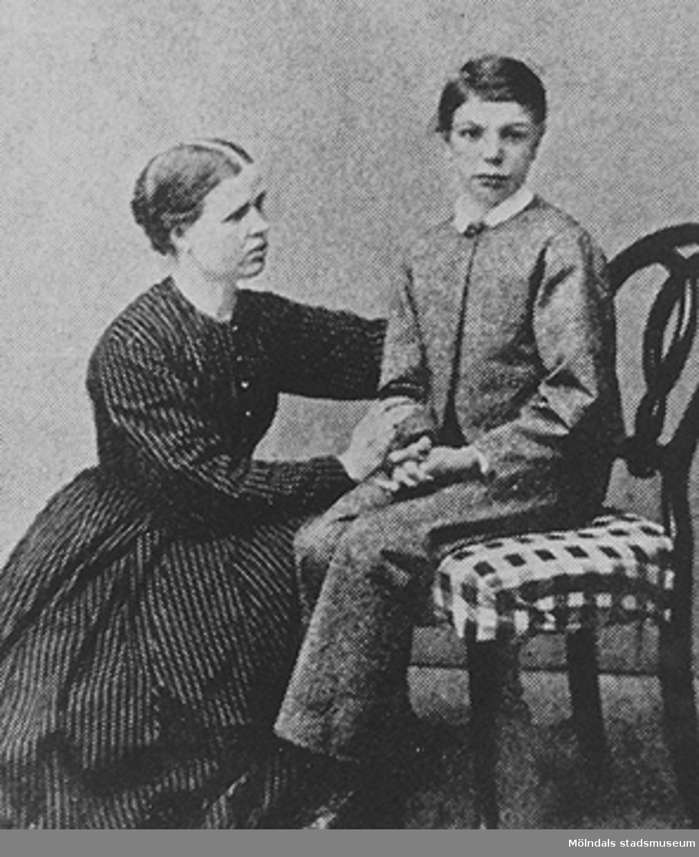 En kvinna liggandes på knä, håller i och tittar på en gosse som sitter på en stol. Okända personer och årtal.