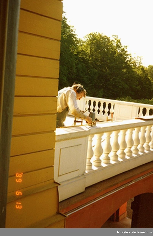 En man står och slipar räcket på balkongen.