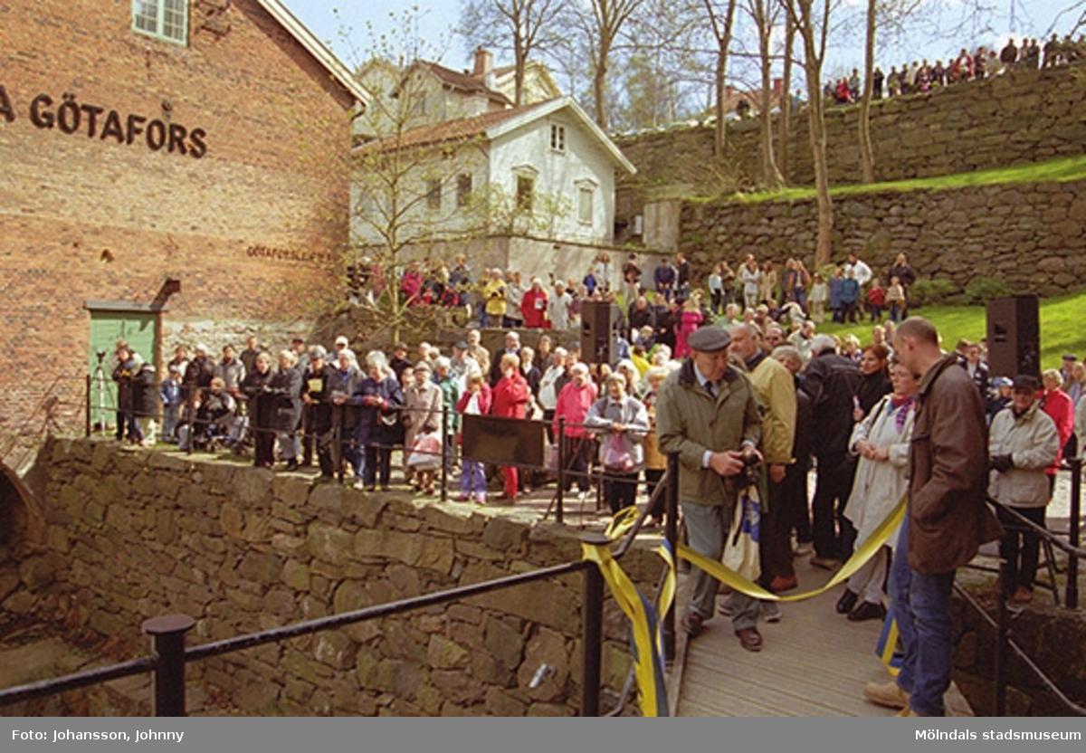 Åskådare utanför Lilla Götafors som väntar på invigningen av Royens spång. Hembygdsföreningens ordförande Sven-Olof Olsson (med grå keps) samt antikvarie Ulla Hasselqvist (lutad mot broräcket) står längst fram vid bandet.