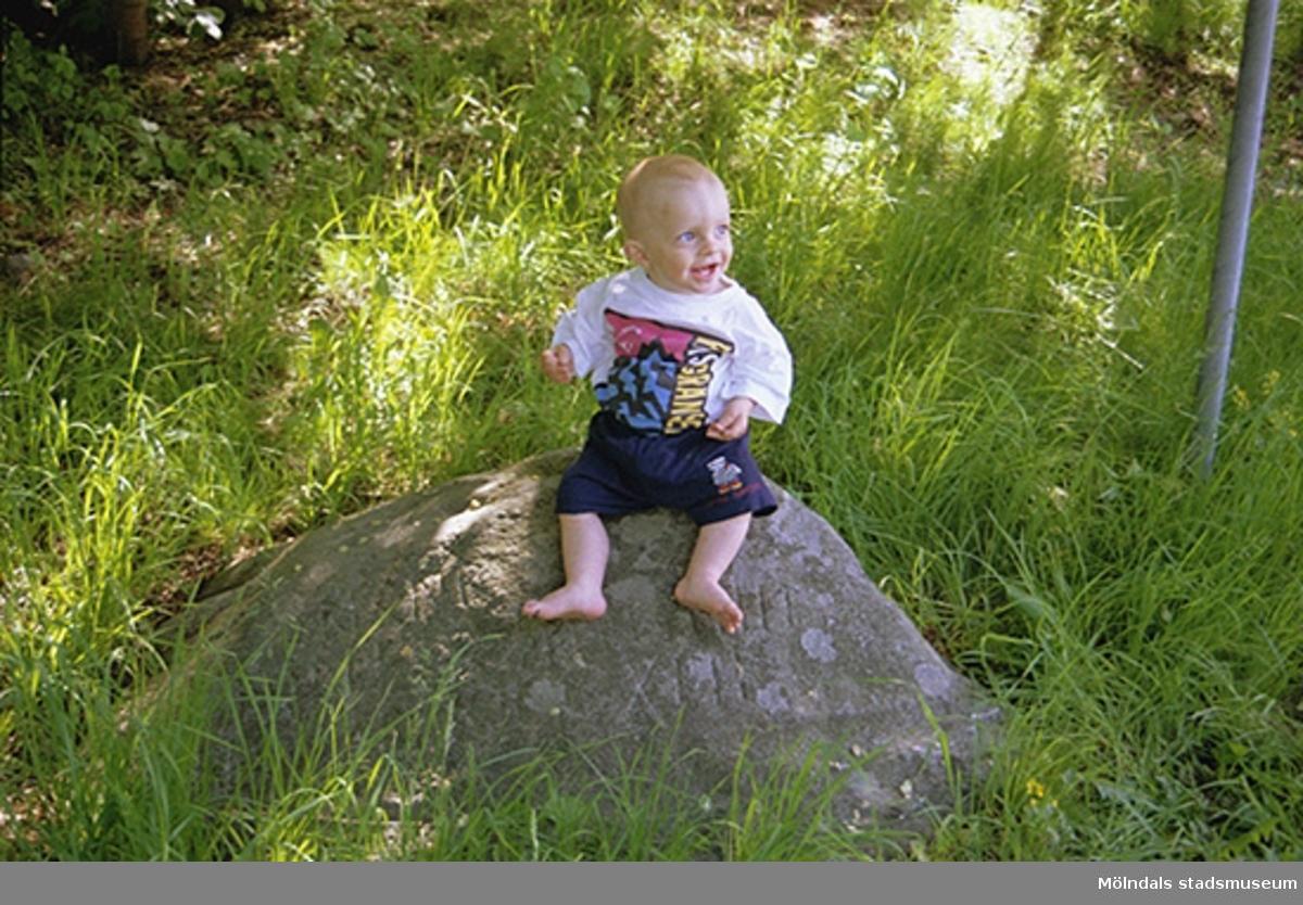 Vy från väster på ett litet barn som sitter på runstenen. Hulelycksgatan i maj 1998.