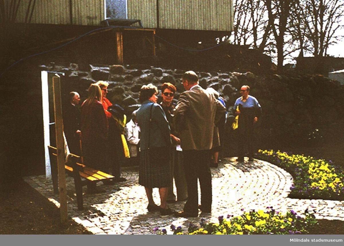 Män och kvinnor kring en bänk vid Lyktplatsen i Kvarnbyn.  Gatyktan invigs på Kvarnbydagen 25/4-1993.