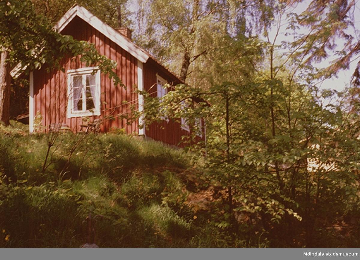 """En röd stuga i området söder om Fässbergs kyrkogård, alldeles intill """"Fässberget"""", maj 1993."""