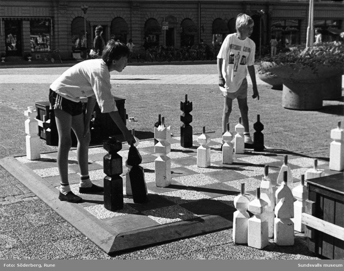 Pojkar spelar schack på Stora Torget.