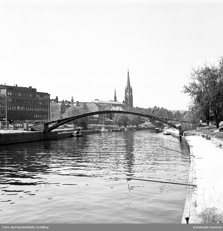 Gamla puckelbron över Selångersån med kyrkan i bakgrunden.