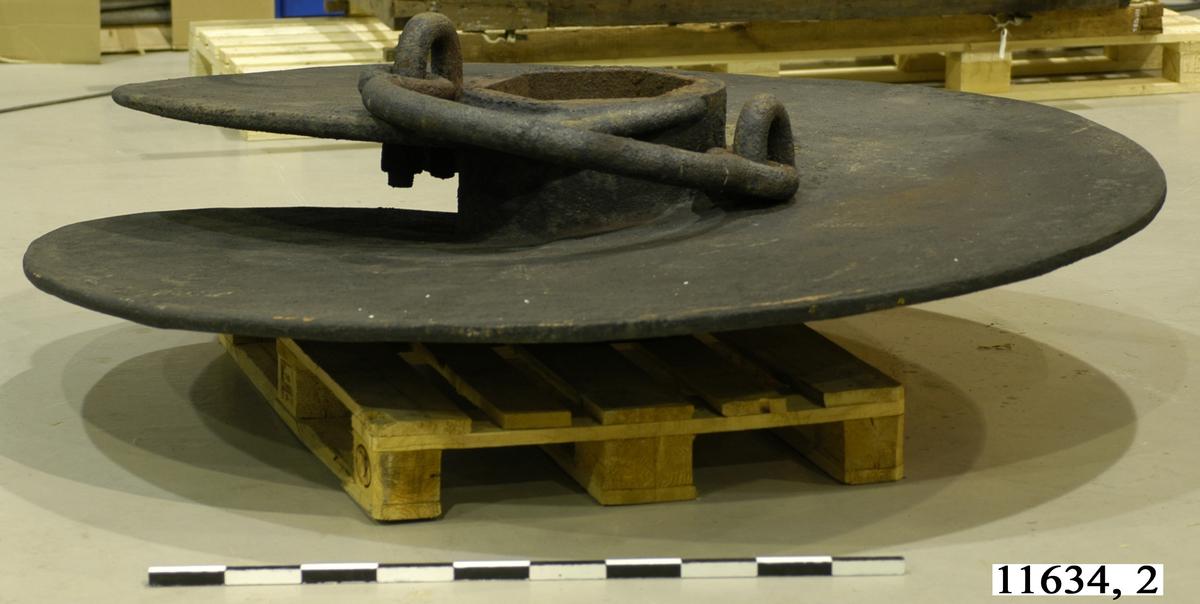 Skruvankare, ursprungligen två skruvpropellrar. Har formen av en skruvpropeller. I mitten en sexkantig kona för propelleraxeln. Gjutna av tackjärn.  Kompletterande dimensioner: Avståndet mellan de parallella ytorna = 300 mm Ytans bredd i överkanten = 175 mm