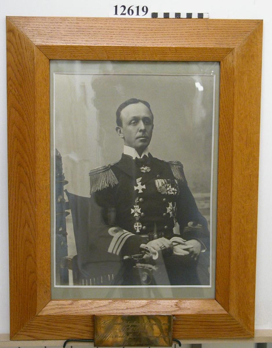 Fotofrafi, person- Inom glas och ram av ek. Text på namnplåt av försilvrad mässing: Kommendörkapten af 1 graden m.m. T.M. Peyron t. f. chef för Underofficers- och sjömanskårerna 1/3 - 30/9 1911.