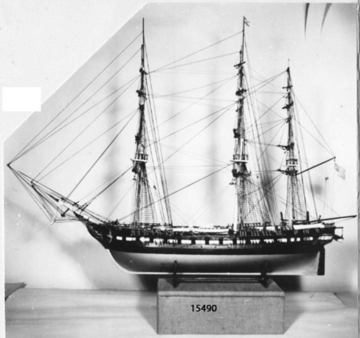 Constitution, fregatt. Tremastad fartygsmodell av plast, svart skrov med vitt fält i linje med kanonportarna.