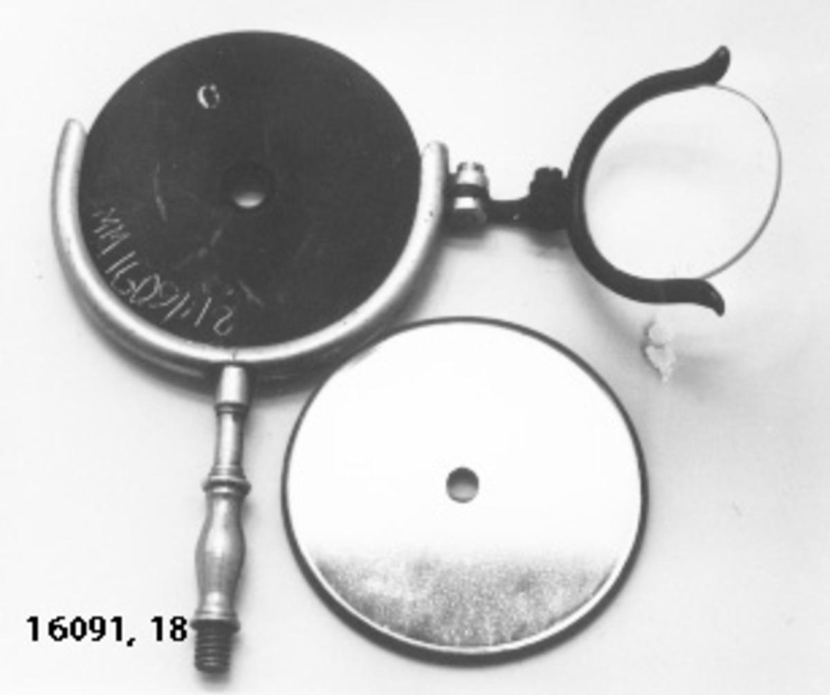 Ögonspegel. I en halvcirkelformad ställning med skaft med i ena kanten vridbart förstoringsglas, fästes någon av de två tillhörande speglar med i mitten ett hål. Speglarna cirkelrunda, svart baksida och ingraverad bokstav i vitt: C eller P.