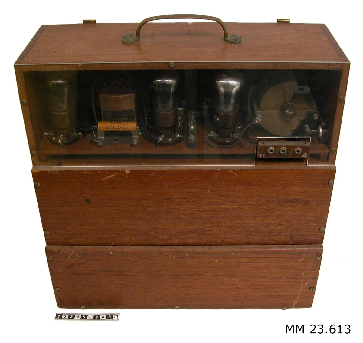 """Rörvågmeter monterad i trälåda med ett bärhandtag av mässing på ovansidan.  Den raktangulära lådan är upptill på framsidan försedd med ett plexiglasfönster varigenom det går att se instrumentets delar såsom lampor och metalldetaljer. I fönstrets nedre högra hörn finns tre stycken anslutningsöppningar. På baksidan sitter instrumentets manöverdon. Där finns ett antal manöverspakar märkta """"Till"""" och """"Från"""" samt två stycken visare med vit och ljusgul visarbakgrund. I manöverkontrollens nederkant sitter en transparant lampa. Under kontrollpanelen finns ett utrymme varifrån det går två stycken tygklädda kablar försedda med en klämma i respektive ände. Till utrymmet finns en lucka som på insidan är tryckt i vitt med tre kronor och under dessa finns ett """"M"""". Luckan är inte komplett utan bara en del av baksidan täcks av den."""