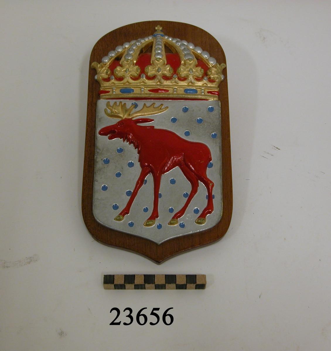Vapensköld, Gästrikland, storlek B. Vapensköld av gjuten mässing, i ett med blå kulor bestrött fält av silver en röd älg med gyllene krona. Krönt med kunglig krona. Monterad på fernissad platta av mahogny.