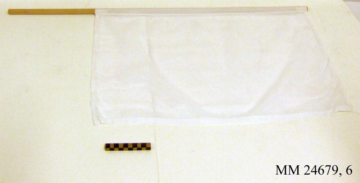 Manöverflagga på stång av trä. Flagga av vit nylon. Vitt lik trätt över rundstaven och fäst med häftklammer. Flaggan ligger i påse tillsammans med fem andra flaggor, sk. manöverflaggställ.
