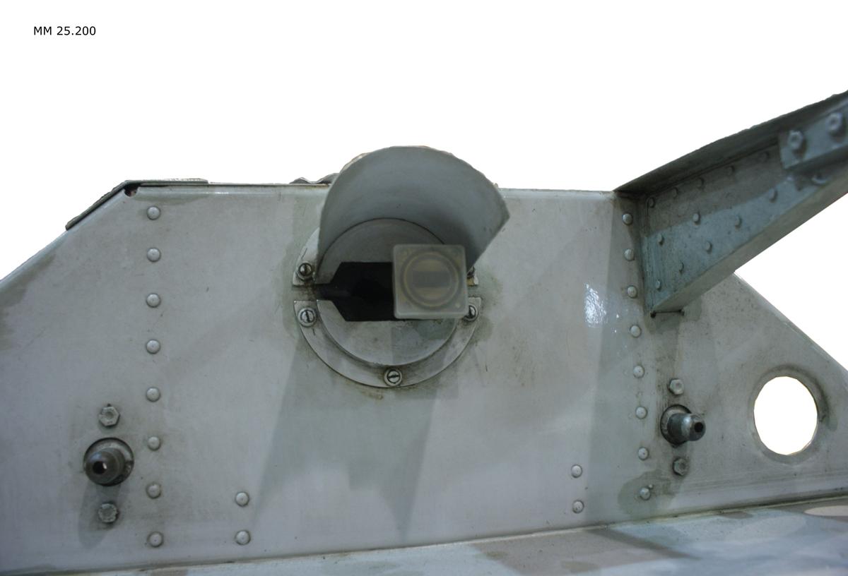"""Antennfäste till radar PS864 med tillhörande antenndom. Radarfästet cirkelrunt i grå metall med upphöjning med flera armar på. Text: """"Trampa ej här"""". På en grå och svart liten skylt återfinns uppgifter om förrådsbeteckning F3503-000259, vilket är själva antennfästet. Därunder ett gult klistermärke med svart text """"3"""" vilket anger individnummer. Under antennfästet sitter en grön halvsfär som utgör radomen med texten: """"Hanteras varsamt""""."""
