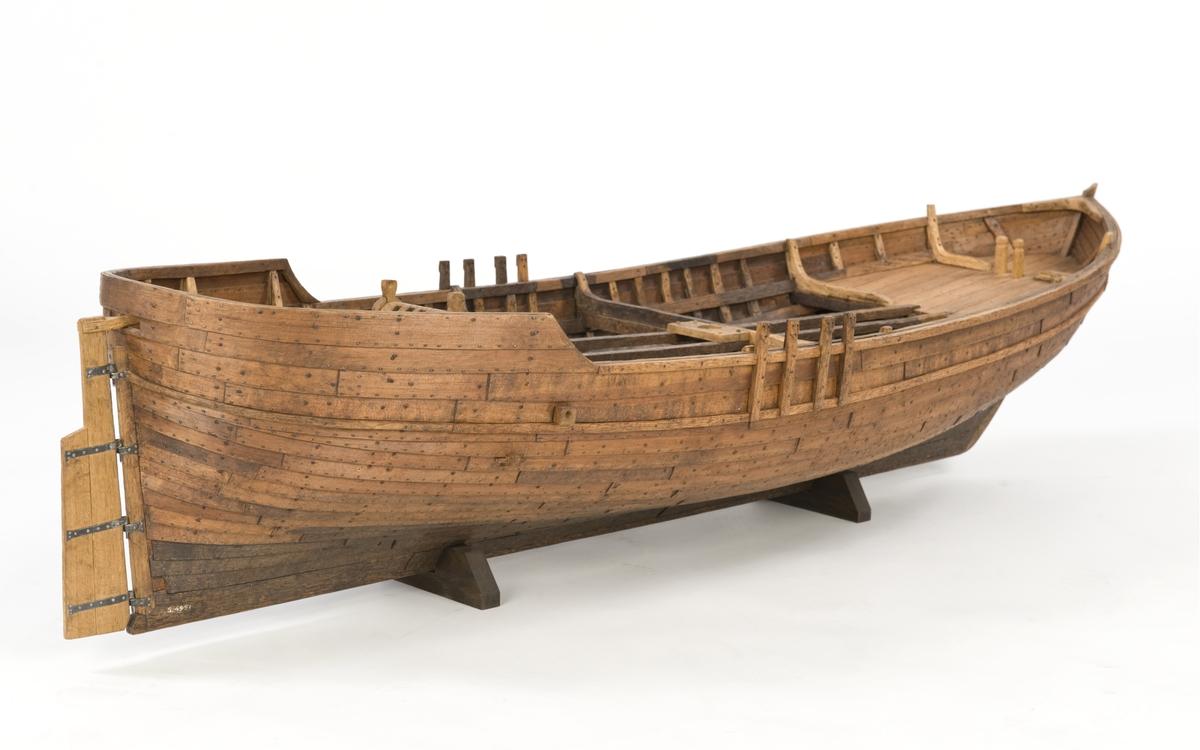 Fartygsmodell. Lastskuta från 1500-talet, klinkbyggd med sjutton bord på var sida, odäckad med back och akterdäck. Skrovet betsat ljust och mörkt. Pump och roder, röstjärn av trä, ankare och riggad mast.