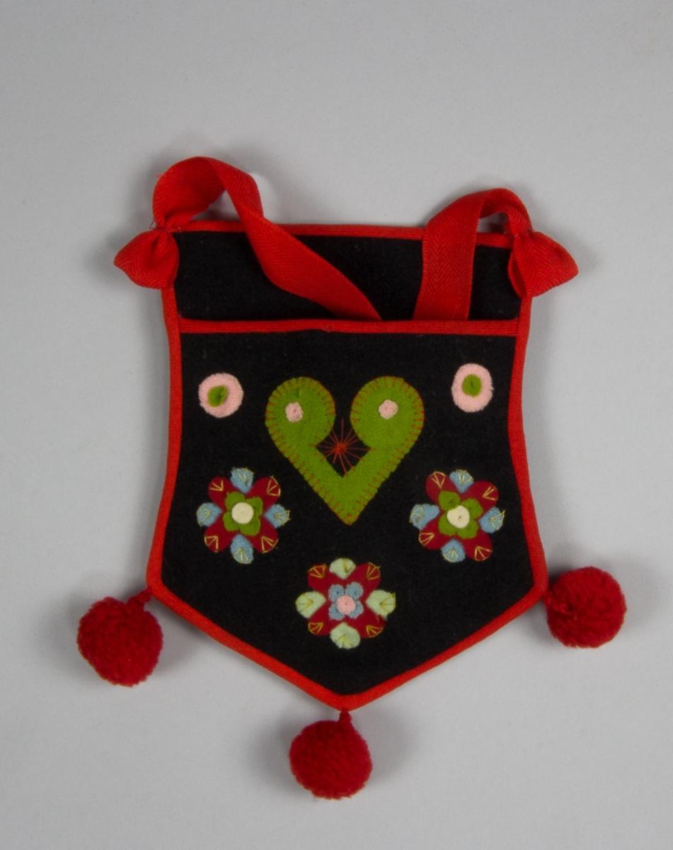 Kjolsäck inspirerad av dräkt för kvinna från Rättviks socken, Dalarna. Modell med avskuret framstycke. Tillverkad av mörkgrått ylletyg, vadmal, med applikationer av tunnt ylletyg, flanell, i grönt, rött, ljusblått, rosa och vitt, fastsydda med bomullstråd och langettsöm. Centralt placerad hjärtfigur omgiven av blomfigurer och rundlar. Broderi sytt med bomullstråd i flera färger, sticksöm. Kantad runtom med rött diagonalvävt ylleband. I nederkanten fäst tre bollar av ullgarn. Bakstycke av samma vadmal som framstycket. Axel- eller midjeband av fabriksvävt rött ylle, vävt i spetskypert.
