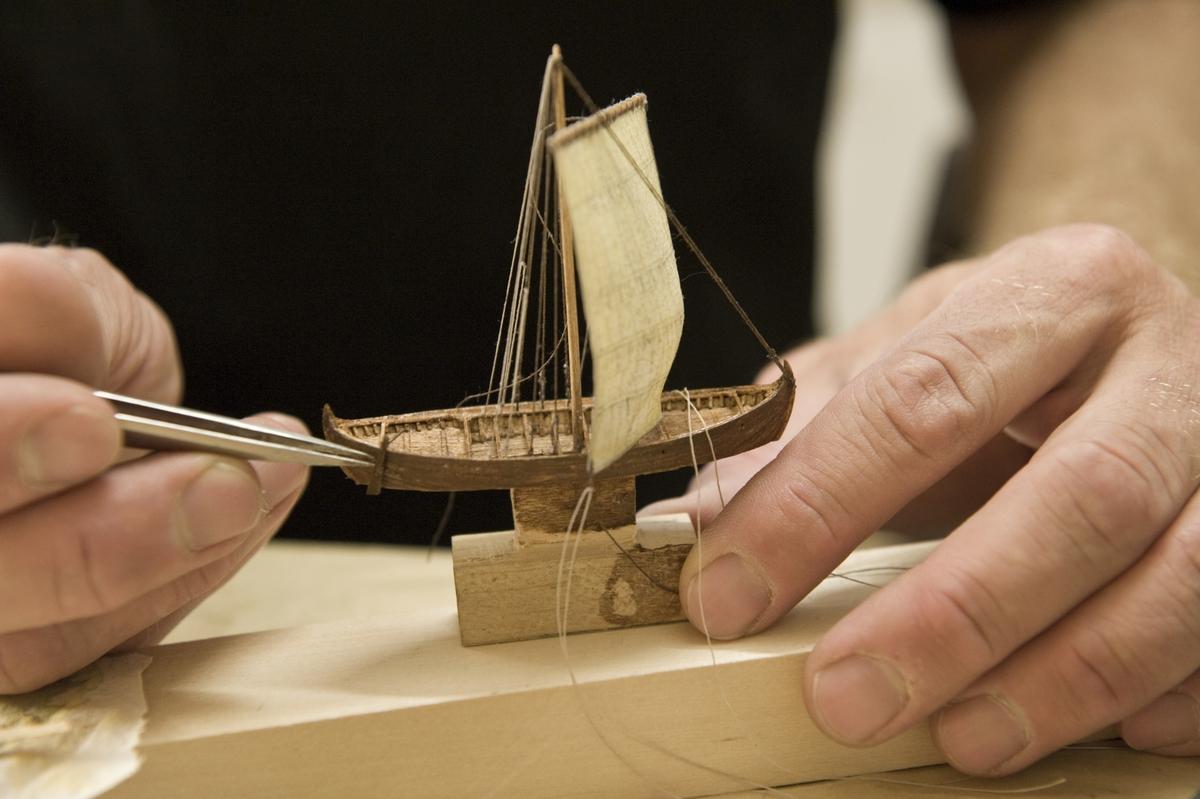 """Modellbyggare Stefan Brun i arbete med en modell i skala 1:200 till utställningen """"Shipping & Shopping""""."""
