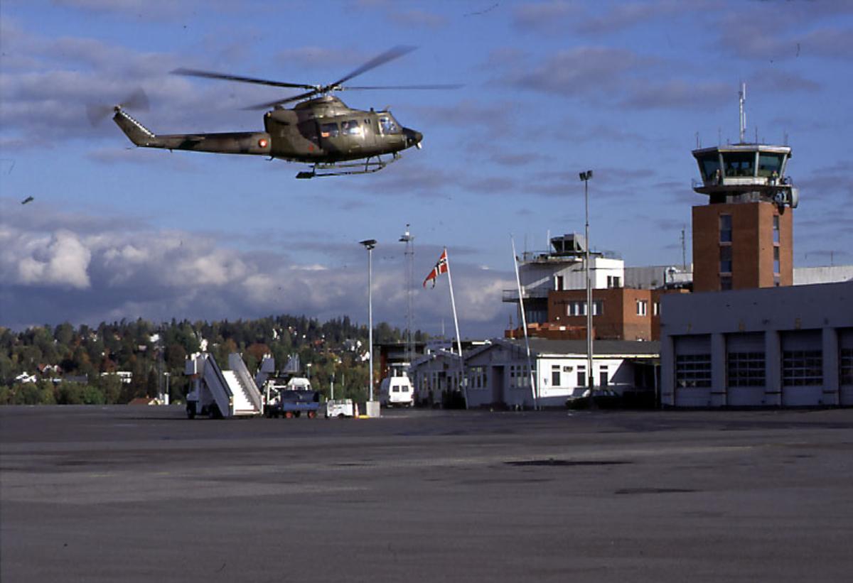 Lufthavn, 1 helikopter, Bell 412, 147 fra RNoAF, i luften.  2 kjøretøy, kontrolltårnet og andre flyplassbygninger i bakgrunnen.