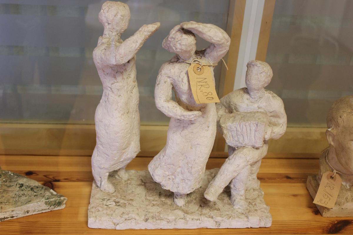 """Skulptur i gips av to mennesker som danser og en som spiller trekkspill. Tittel: """"Dans på brygga"""" fra 1936. Se også nr.196"""