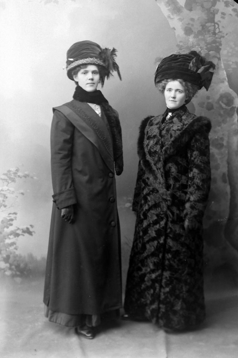 Atelierportrett av to kvinner i helfigur.