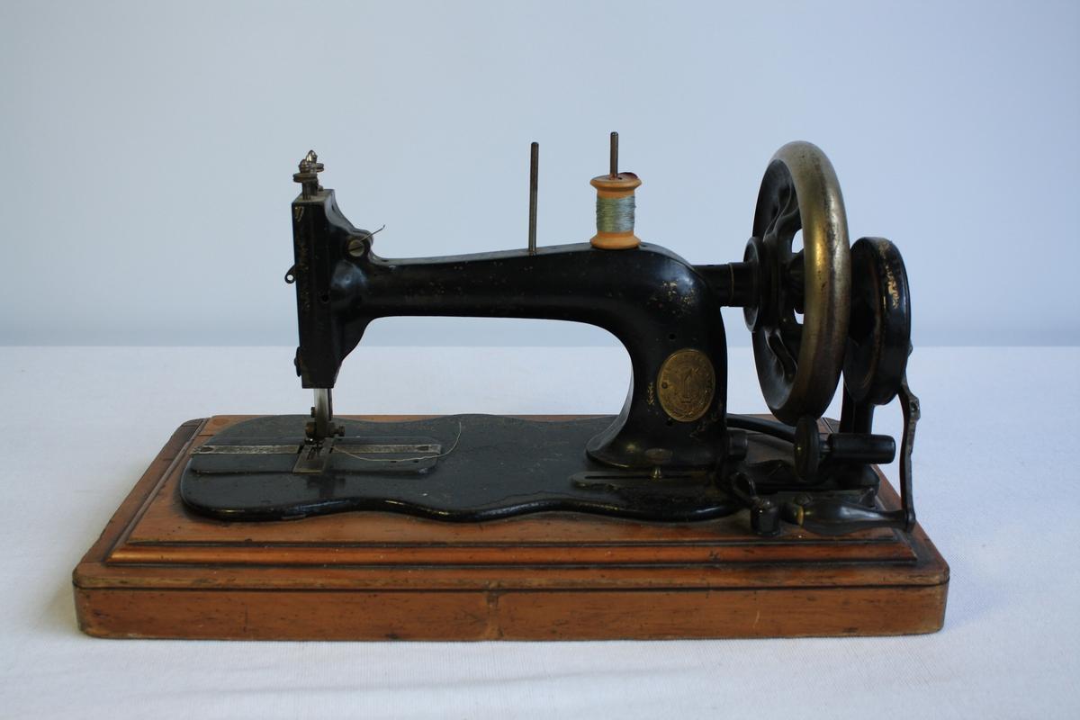 Symaskin med handsveiv på tresokkel.