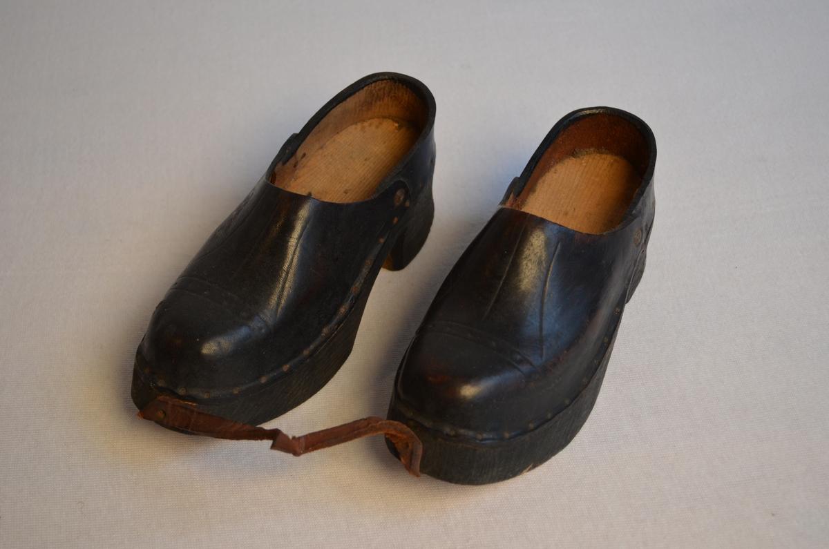 1 par sko med tresole og lær over. Skorne er festa saman med ei lærreim i framkant. Skorne har hælkappe. Enkel dekor på overlær.