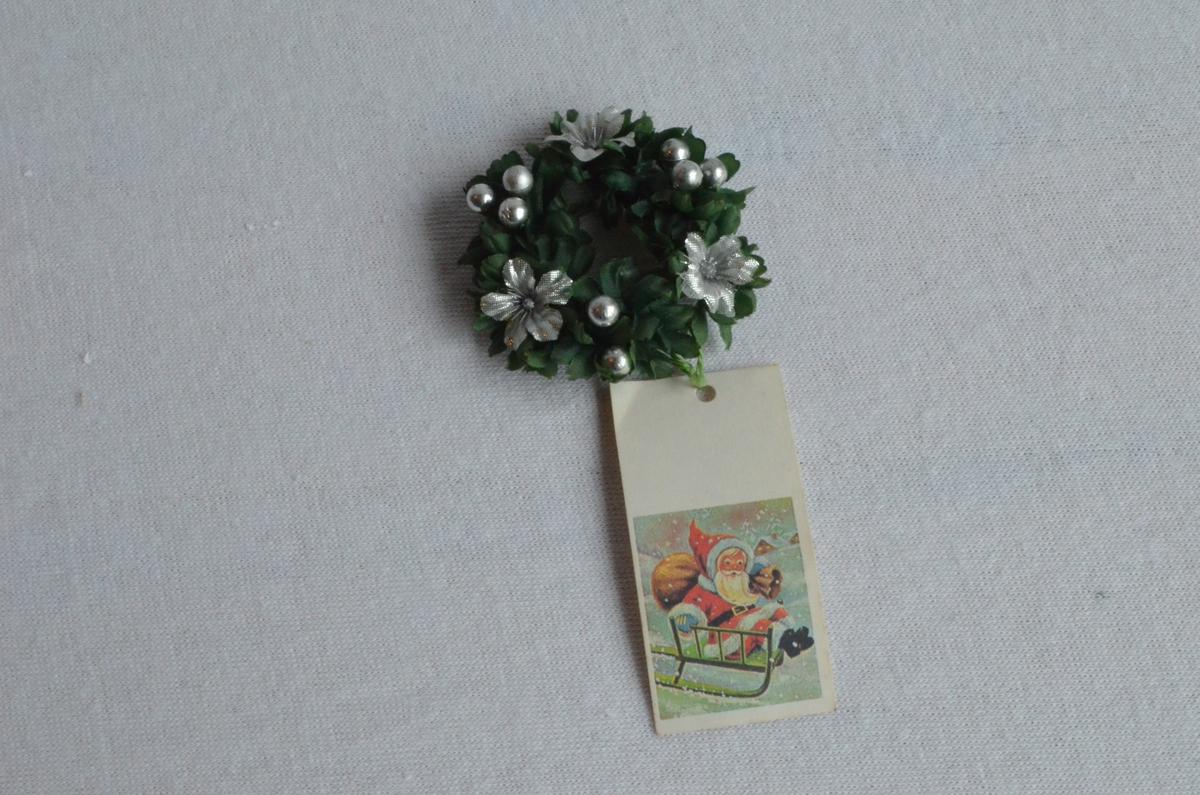 Lysmansjett i grønt og sølv. Grøne blad og bær og blomar i sølv. Alt i plast. På undersida heng det eit klistermerke der det står Made in China. Det heng også ved ein til og fra lapp med julemotiv. Motivet er ein nisse med sekk på ein grøn slede.