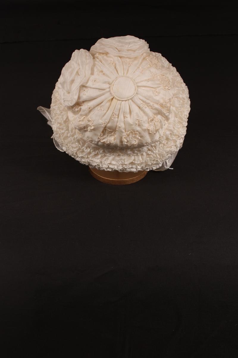 Form: Rund pull, innvendig trekt med gas. maskinbrodert silkestoff utanpå, eittstykke rynka saman i midten. Stor pyntekant rundt heile hua, fyllt med bomull el.l. Midt framme to store silkerosettar. Knyteband under haka av breie silkesløyfer.