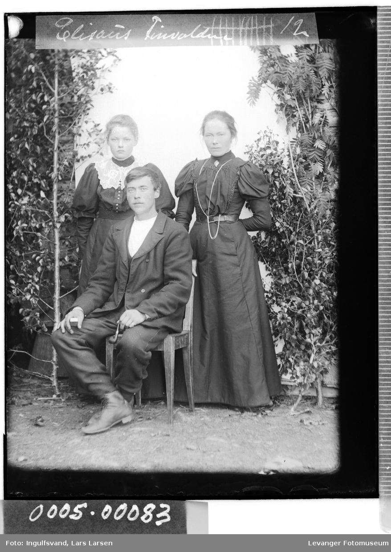 Gruppebilde av to kvinner, den ene ganske ung og en mann som sitter.