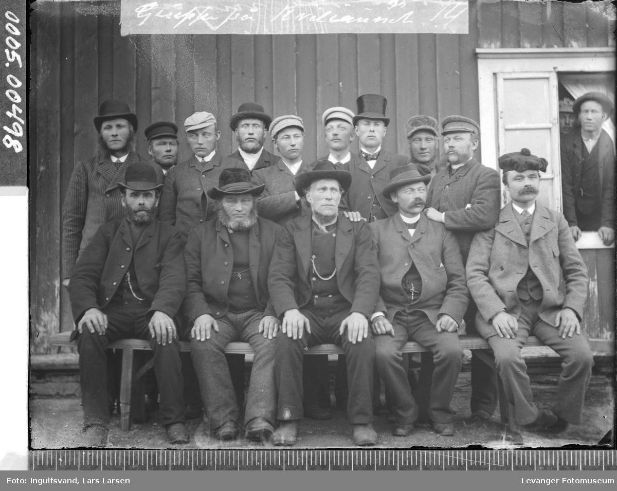 Gruppebilde av fjorten menn foran en vegg.