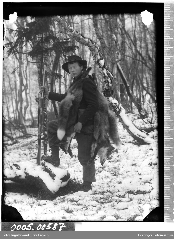 Portrett av en jeger bærende på gevær og døde rever.