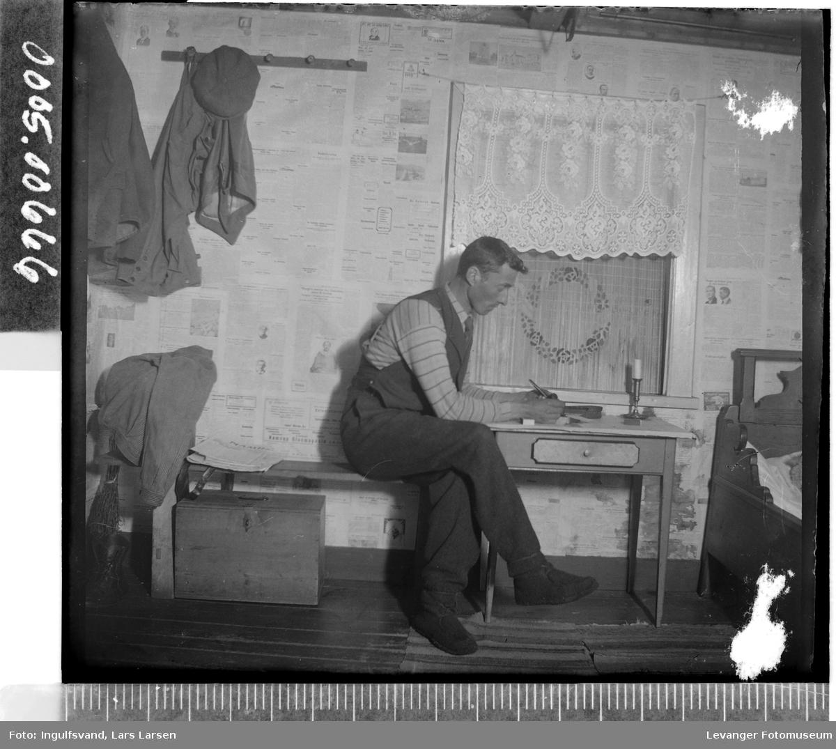 Mann som sitter ved et skrivebord.