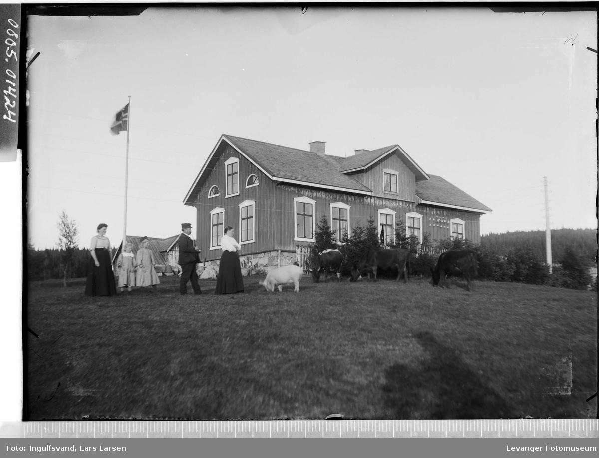 Skolebygning med to kvinner, en mann, to barn og husdyr i forgrunnen.