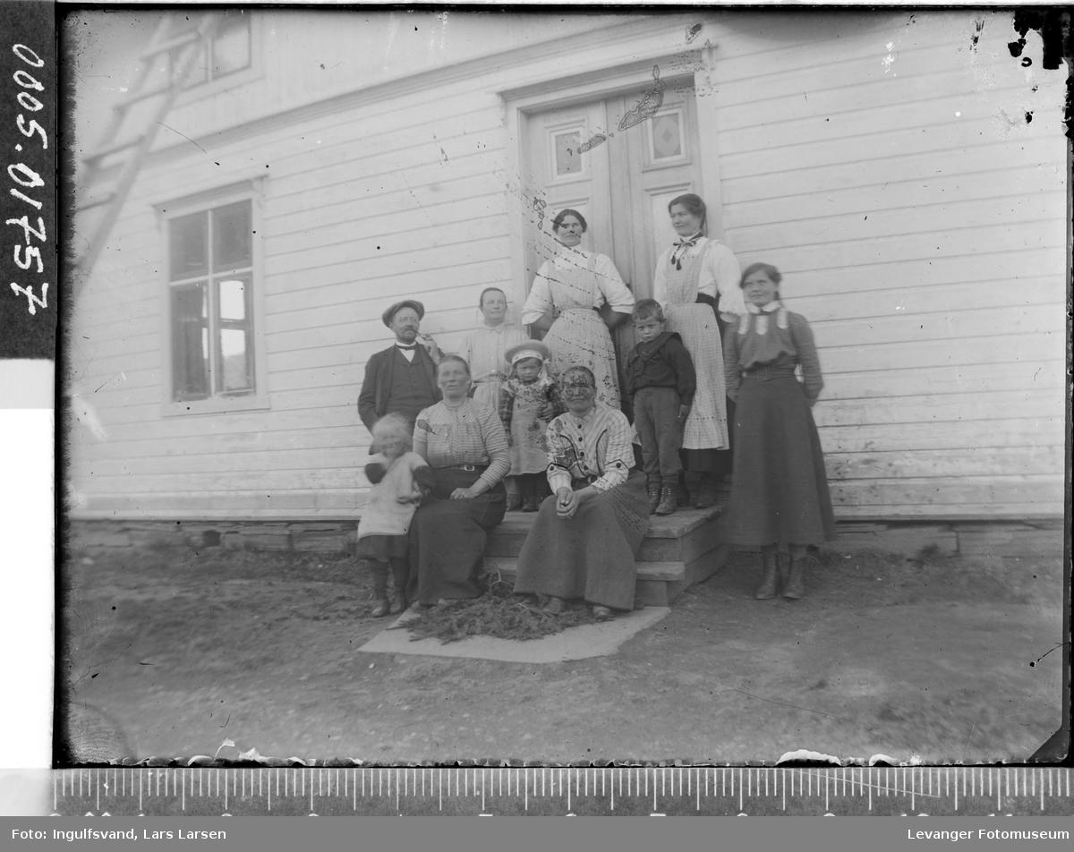 Gruppebilde av ti menn, kvinner og barn foran et inngangsparti.