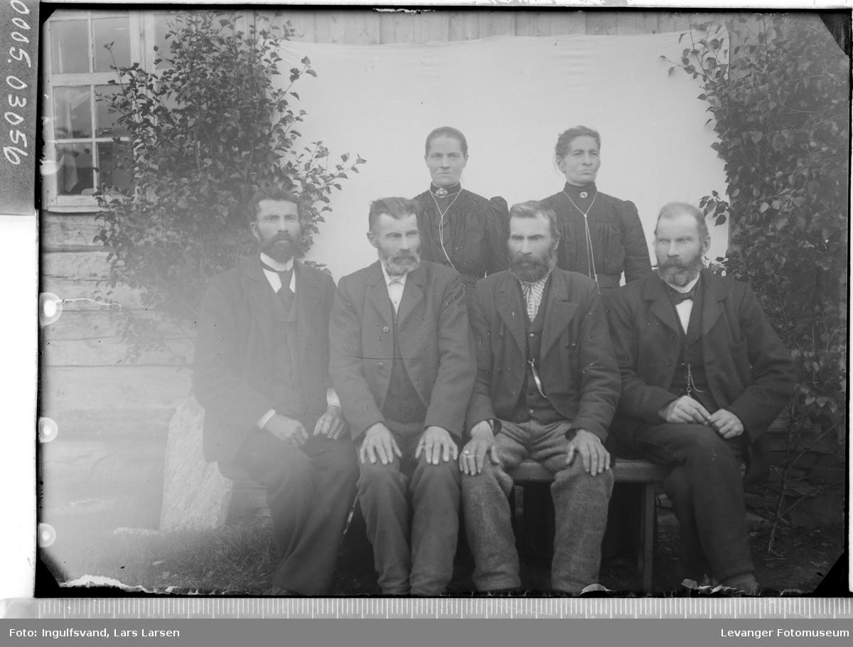 Gruppebilde av fire sittende menn og to kvinner.