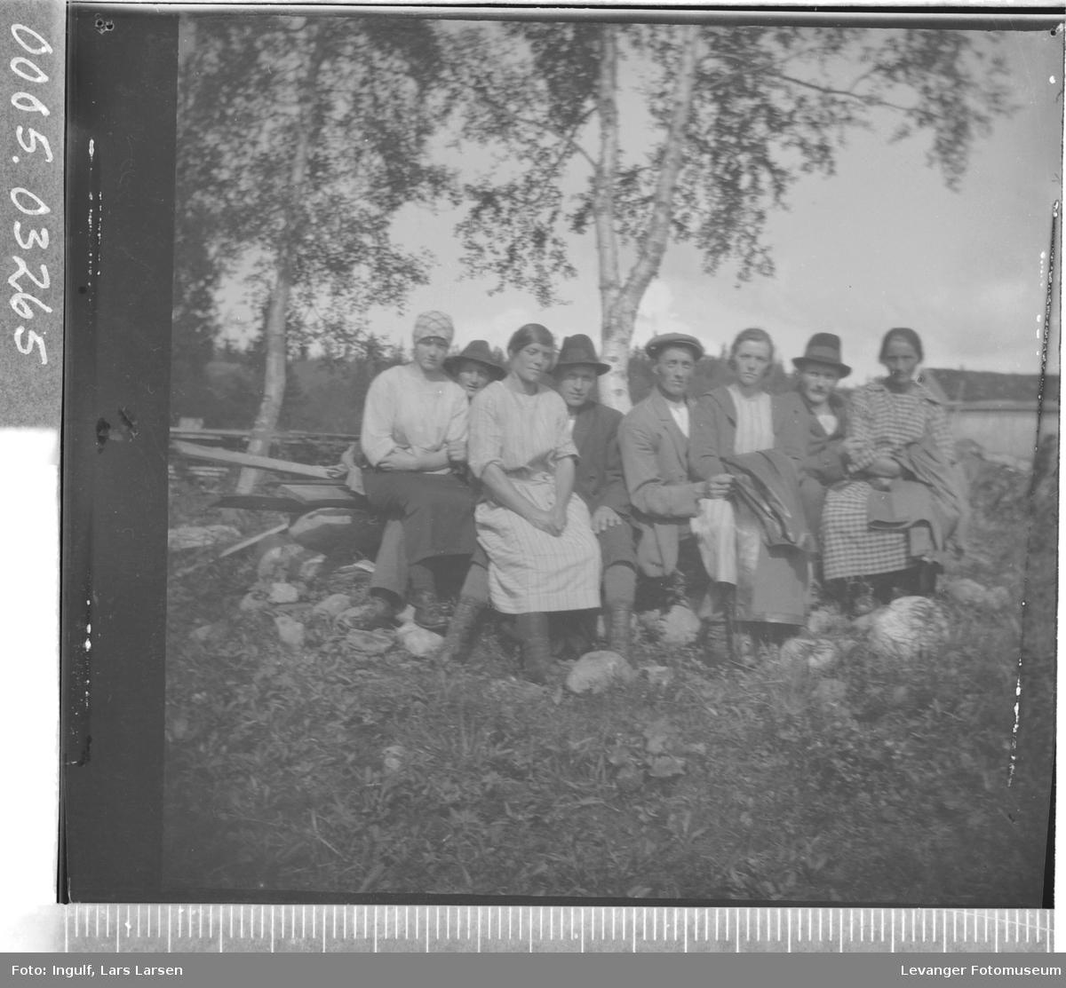 Gruppebilde av fire kvinner og fire menn som sitter på en steinrøys.
