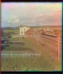 Levanger jernbanestasjon med grønnsakshager i forgrunnen, se